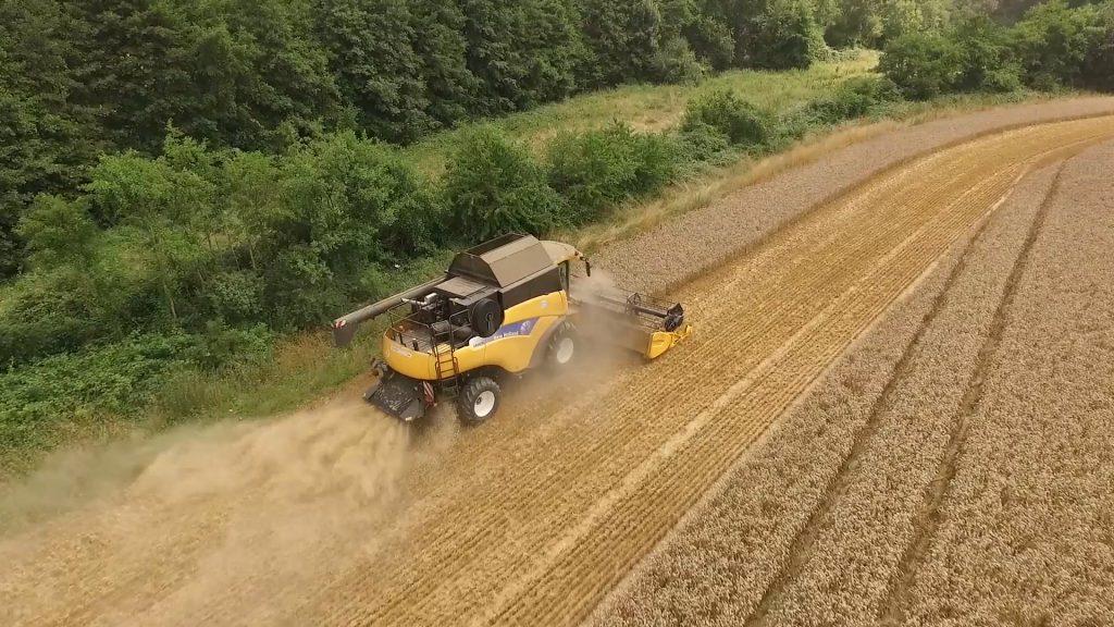 Photo prise par un drone d'une moissonneuse dans un champ de blé