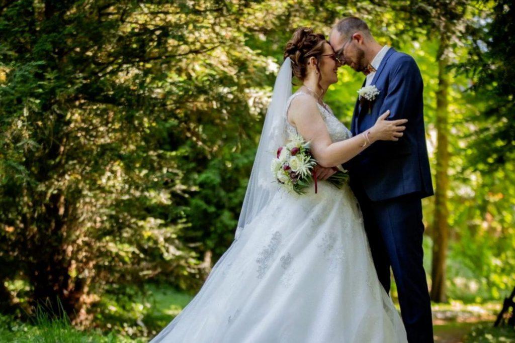 Un couple de mariés s'enlace devant une forêt