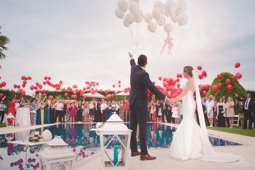 Un couple de mariés lance des ballons devant leurs invités