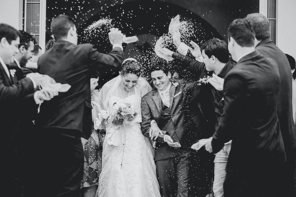 Un groupe de personne lance du riz sur un couple de mariés