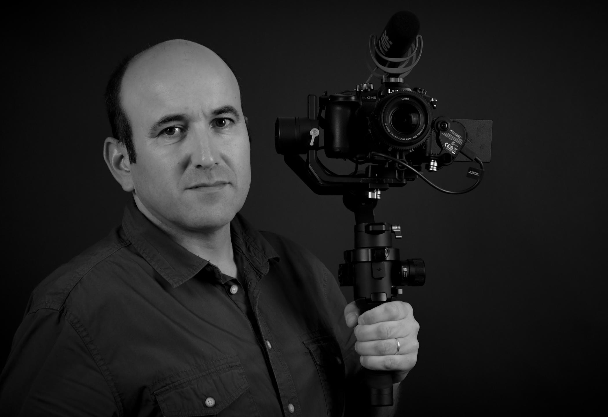 portrait de Damien Angier portant un appareil photographique